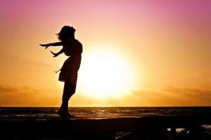 Femme debout bras écartés respirant au soleil levant